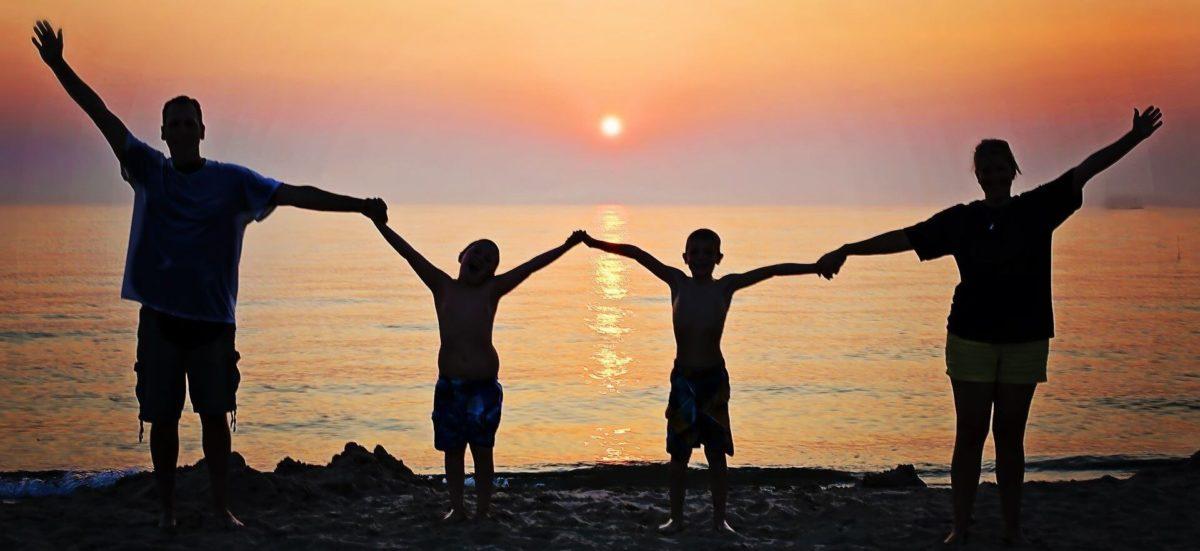 Silhouette einer glücklichen Familie im Gegenlicht eines Sonnenuntergangs